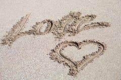 Aimez écrit sur le sable avec un dessin de foyer Photo libre de droits