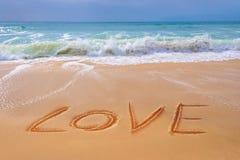 Aimez écrit sur le sable d'une plage, jour de valentines Photographie stock