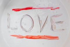 Aimez, attribuez un libelle le rouge d'amour de mot dans la surface de couleur Photo libre de droits