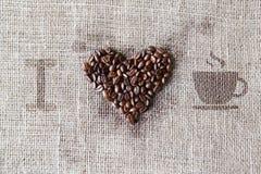 Aimez au café - texture de toile de jute avec la forme de coeur de haricots Photos stock