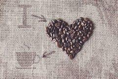 Aimez au café - texture de toile de jute avec la forme de coeur de haricots Photographie stock libre de droits