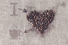 Aimez au café - texture de toile de jute avec la forme de coeur de haricots Images stock