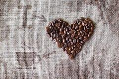 Aimez au café - texture de toile de jute avec la forme de coeur de haricots Photographie stock