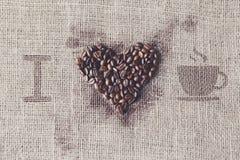 Aimez au café - texture de toile de jute avec la forme de coeur de haricots Photo libre de droits