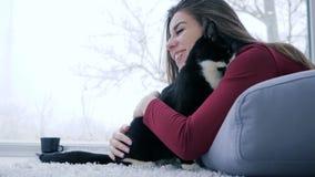 Aimez aux animaux, repos femelle mignon avec le chat à la maison sur le fond de la fenêtre panoramique clips vidéos