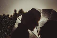Aimez dans la pluie/silhouette des couples de baiser sous le parapluie Photographie stock libre de droits