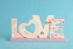 Aimez dans les lettres roses d'isolement sur un fond bleu Photos stock