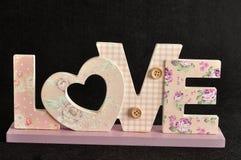 Aimez dans les lettres roses d'isolement sur un fond noir Photos stock