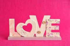 Aimez dans les lettres roses d'isolement sur un fond rose Photo stock