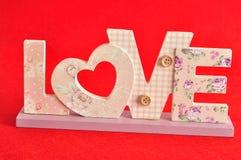 Aimez dans les lettres roses d'isolement sur un fond rouge Photo stock