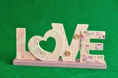 Aimez dans les lettres roses d'isolement sur un fond vert Photographie stock