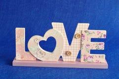 Aimez dans les lettres roses sur un fond bleu Photographie stock