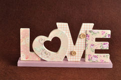 Aimez dans les lettres roses sur un fond brun Photos stock