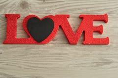 Aimez dans les lettres rouges avec un petit coeur noir Photo stock