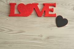 Aimez dans les lettres rouges avec un petit coeur noir Image stock
