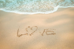 Aimez l'écriture de main de message sur la plage de sable Images libres de droits