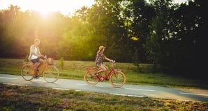Aimez l'équitation de couples sur des bicyclettes de vintage en parc Photos libres de droits