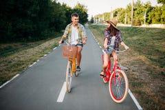 Aimez l'équitation de couples sur de rétros vélos en parc d'été Images libres de droits