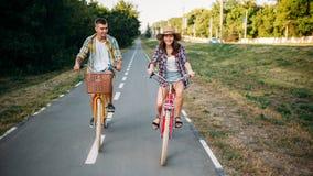 Aimez l'équitation de couples sur de rétros vélos en parc d'été Photo libre de droits