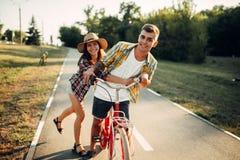 Aimez l'amusement de couples en parc d'été, bicyclette de vintage Images libres de droits