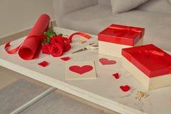 Aimez l'emballage cadeau avec les rouleaux de papier et le bouquet des roses Image stock