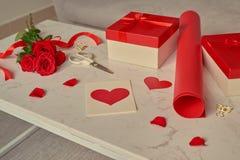 Aimez l'emballage cadeau avec les rouleaux de papier et le bouquet des roses Photos libres de droits