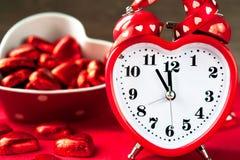 Aimez l'horloge rouge de forme de coeur et les chocolats sucrés Heure pour l'amour Image stock