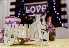Aimez l'inscription sur un fond en bois, des lumières clignotantes et des fleurs Vélo en gros plan de jouet Images stock