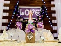 Aimez l'inscription sur un fond en bois, lumières clignotantes, fleurs Bouteille de champagne et de glaces Photographie stock