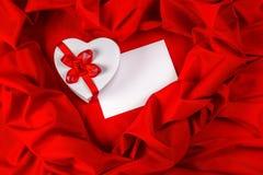 Aimez la carte de voeux avec le coeur sur un tissu rouge Image libre de droits