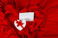 Aimez la carte de voeux avec le coeur sur un tissu rouge Images libres de droits