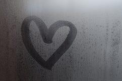 Aimez la forme de coeur tirée par la main sur le carreau de fenêtre humide et congelé avec le fond de lumière du soleil de matin  Photographie stock libre de droits