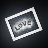 Aimez la forme de mot faite de sucre dans le cadre blanc sur le fond noir Photo stock