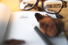 Aimez la lettre de mot sur le livre blanc avec le vieux brun witered defocused Image libre de droits