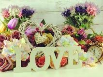 Aimez la lettre en bois de mot avec le décor de fleurs artificielles Image libre de droits