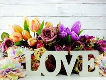 Aimez la lettre en bois de mot avec le décor de fleurs artificielles Photo libre de droits
