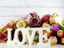 Aimez la lettre en bois de mot avec le décor de fleurs artificielles Photo stock