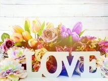 Aimez la lettre en bois de mot avec le décor de fleurs artificielles Image stock