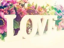 Aimez la lettre en bois de mot avec le décor de fleurs artificielles Photographie stock