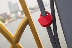 Aimez la serrure de forme de coeur avec la chaîne en métal sur le pont Photographie stock libre de droits