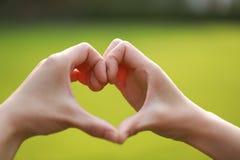 Aimez la silhouette de main de forme dans l'herbe, coeur de main par une main de femme Photos libres de droits