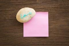 Aimez le caillou de mot avec le bloc-notes vide sur le fond en bois Photos libres de droits