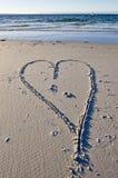 Aimez le coeur dans le sable avec le yacht de fond. Photo libre de droits
