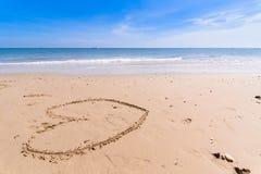 Aimez le coeur dessiné sur le fond atlantique arénacé de côte Images stock