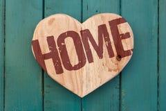 Aimez le coeur en bois de message à la maison sur le fond peint par turquoise Images stock