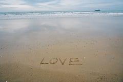 Aimez le concept, écrit à la main en sable sur une plage de mer avec la vague molle Image stock
