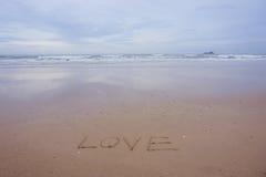 Aimez le concept, écrit à la main en sable sur une plage de mer avec la vague molle Photo stock