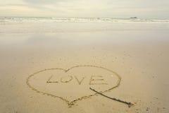 Aimez le concept, écrit à la main en sable sur une plage de mer avec la vague molle Photo libre de droits