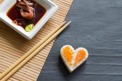 Aimez le concept abstrait de menu de sushi avec le coeur de nigiri sur le fond noir Photographie stock libre de droits