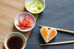 Aimez le concept abstrait de menu de sushi avec le coeur de nigiri sur le fond noir Photographie stock